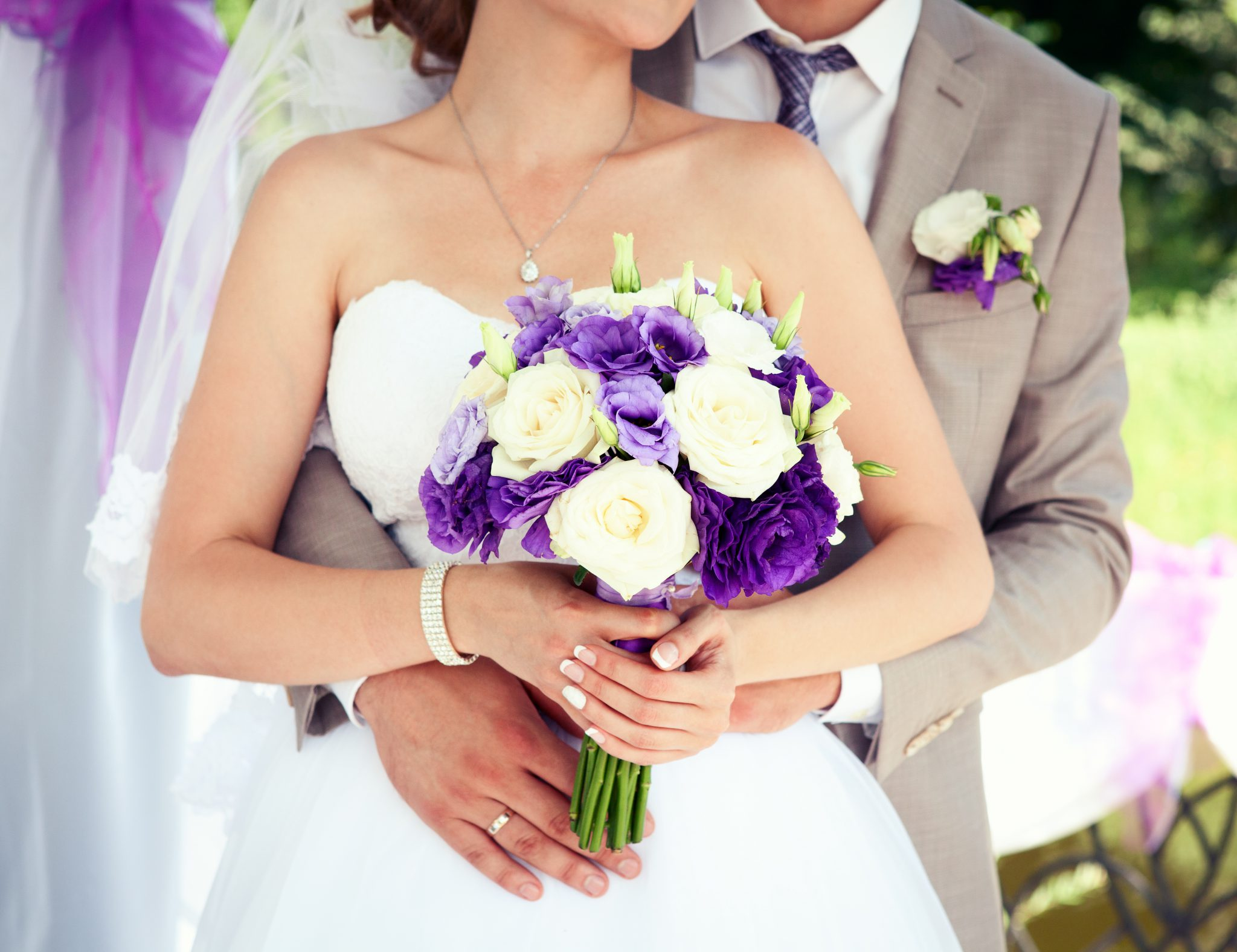 Happy bride and groom on their wedding. Wedding couple bride and groom holding hands.  Wedding bouquet closeup.